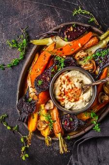 Vegetais cozidos com hummus em um prato escuro, vista superior.