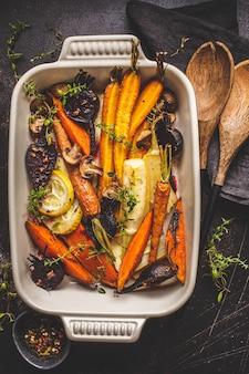 Vegetais cozidos com tomilho no prato do forno, fundo escuro.