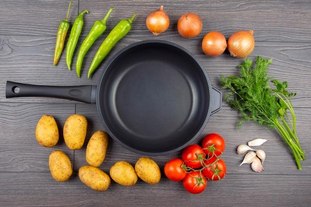 Vegetais crus antes de cozinhar para fritar e refogar em uma panela, vista de cima