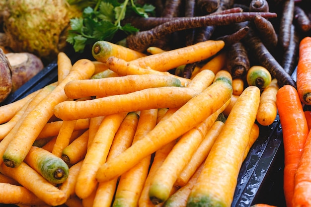 Vegetais crus orgânicos frescos da cenoura crua para a venda no mercado dos fazendeiros. comida vegetariana e conceito de nutrição saudável.