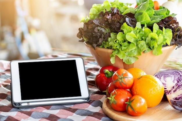 Vegetais crus orgânicos frescos e frutas na tigela para salada e tablet na mesa