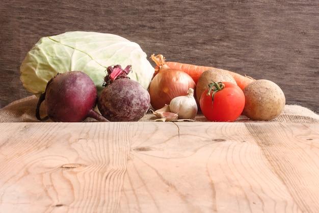 Vegetais crus para o borscht da sopa da beterraba. repolho branco, beterraba, cenoura, batata, tomate, alho em uma placa de madeira