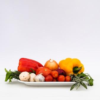 Vegetais crus saudáveis frescos na bandeja no fundo branco
