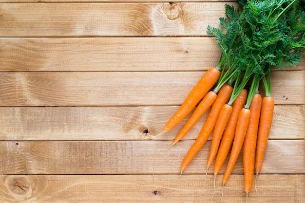 Vegetais de cenoura fresca com folhas no fundo de madeira.