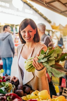 Vegetais de compra da jovem mulher no mercado verde.