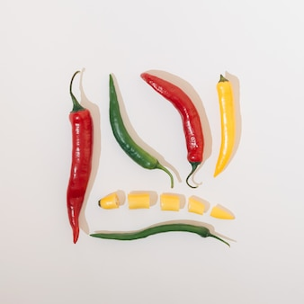 Vegetais de pimentas em várias cores dispostas em uma forma quadrada sobre um fundo branco. conceito de comida Foto Premium