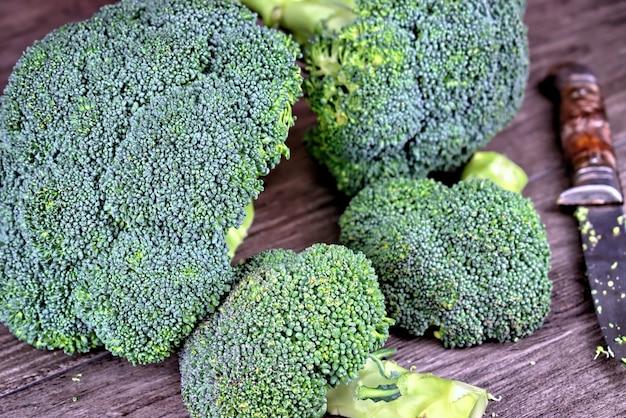 Vegetais, dieta, alimentação saudável e brócolis conceito-verde dos objetos em uma tabela de madeira.