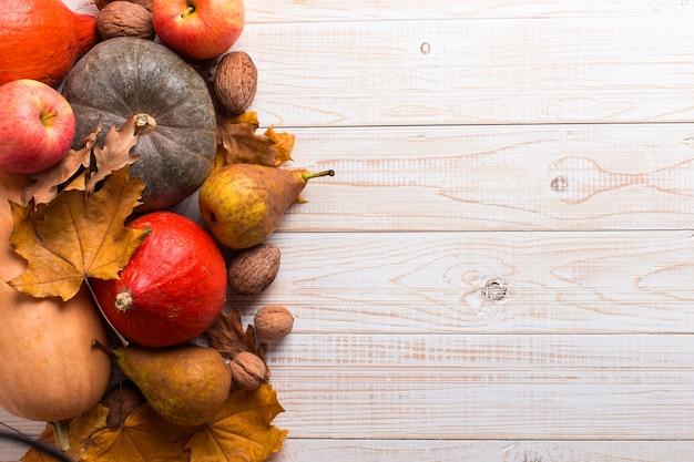 Vegetais diferentes, abóboras, maçãs, peras, nozes e folhas amarelas secas em um fundo de madeira branco, copyspace. colheita.