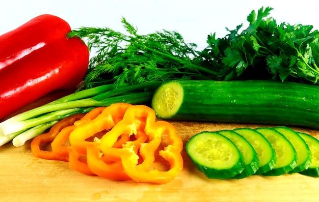Vegetais diferentes em um fundo branco pimenta pepino cebola verde salsa