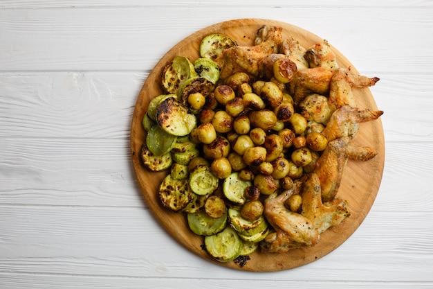 Vegetais e asas de galinha grelhados na placa de madeira. espaço livre.