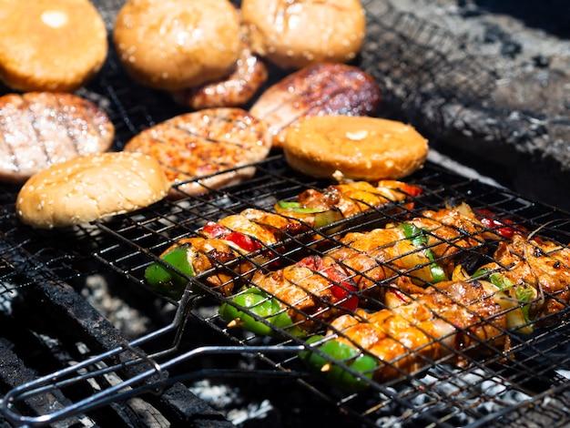 Vegetais e carne fritando no carvão