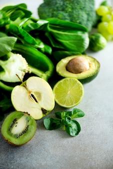 Vegetais e frutas verdes orgânicos no fundo cinzento. maçã verde, alface, pepino, abacate, couve, limão, kiwi, uvas, banana, brócolis