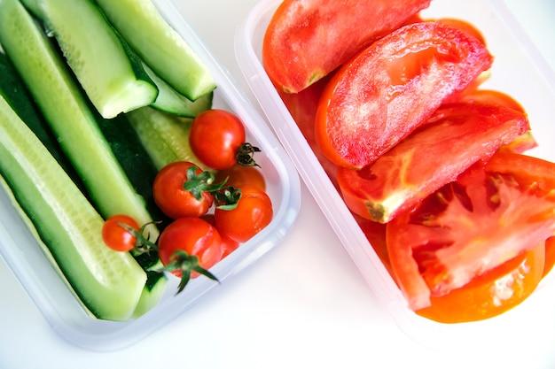 Vegetais fatiados em recipientes plásticos em um fundo branco. pepinos e tomates estão em recipientes.