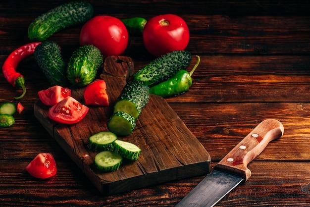 Vegetais fatiados. tomate, pepino e pimentão, mesa de madeira.