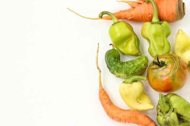 Vegetais feios: cenoura, pepino, pimentão e tomate no fundo branco, conceito de comida feia, foto horizontal, espaço de cópia