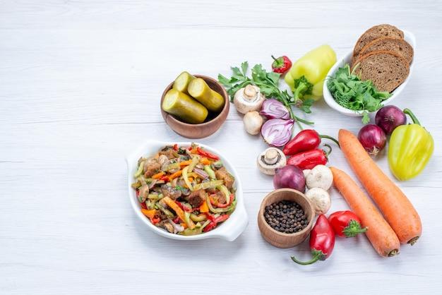 Vegetais frescos, como pimenta, cenoura, cebola com pão e um prato de carne fatiada na mesa branca, vitamina de alimentos vegetais