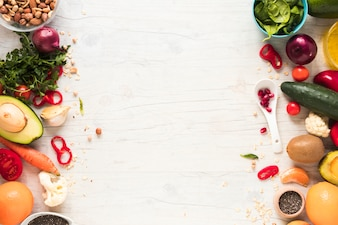 Vegetais frescos; ingredientes e frutas dispostas na mesa de madeira branca