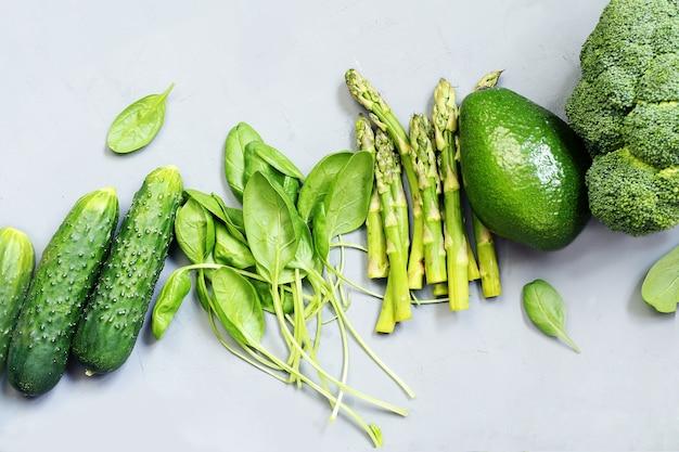 Vegetais frescos verdes abacate brócolis espinafre pepinos em um fundo cinza conceito de comida saudável