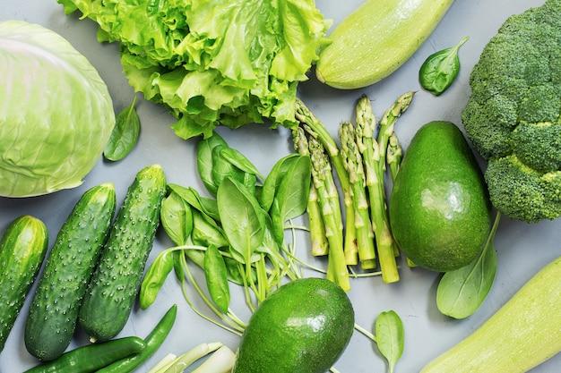 Vegetais frescos verdes abacate brócolis espinafre pepinoscabbagelettuce em um fundo cinza vista de cima conceito de comida saudável
