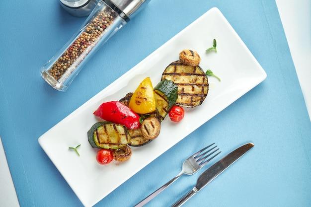 Vegetais grelhados leves e dietéticos, pimentão, abobrinha, cogumelos em um prato branco na toalha de mesa azul.