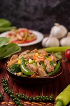 Vegetais mistos fritos com ervilhas, cenouras, cogumelos, milho, brócolis e carne de porco