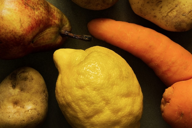 Vegetais orgânicos feios e frutas - cenoura, batata, limão, pêra. produção deformada, conceito de desperdício de alimentos imperfeito deformado. vista do topo.