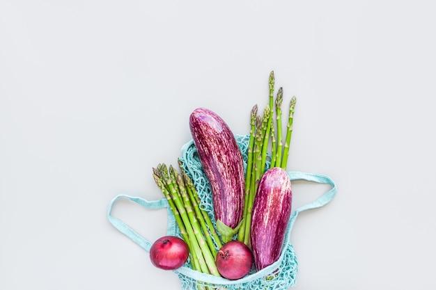 Vegetais orgânicos frescos em uma sacola de compras de malha de algodão reutilizável azul eco