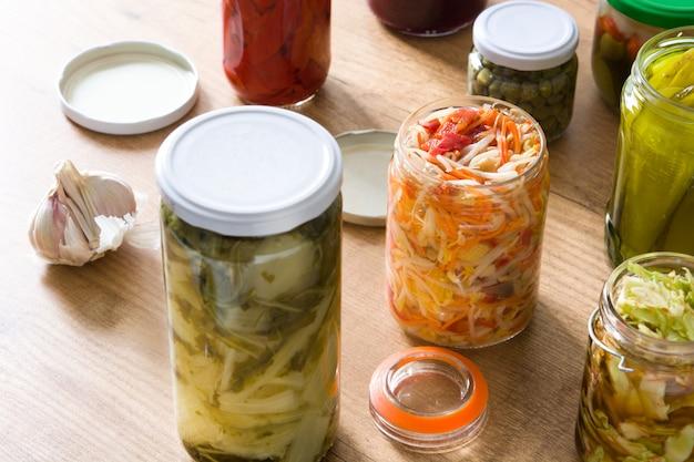Vegetais preservados fermentados em pote na mesa de madeira.