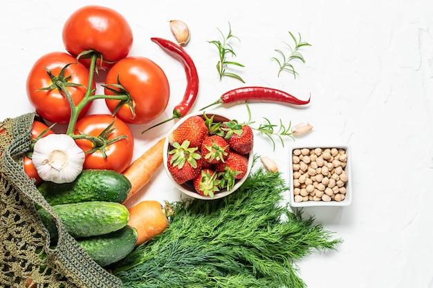 Vegetais saudáveis e orgânicos, frutas e ervas em sacola artesanal reutilizável em fundo branco de concreto.