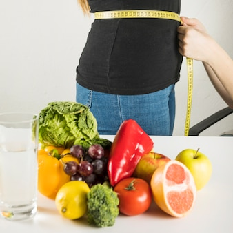 Vegetais saudáveis frescos na frente do nutricionista feminino, examinando o paciente na clínica