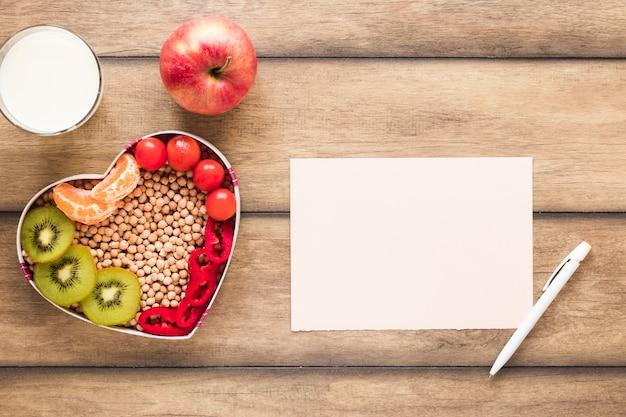 Vegetais saudáveis; frutas; leite com papel em branco e caneta na mesa de madeira