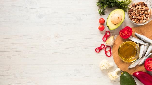 Vegetais saudáveis; frutas secas; óleo e peixe cru na mesa de madeira