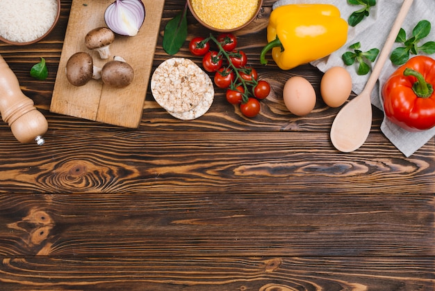 Vegetais saudáveis; ovos; bolo de arroz tufado e polenta na mesa de madeira