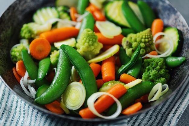 Vegetais veganos na frigideira, fritos ou prontos para cozinhar na mesa. fechar-se. foco seletivo