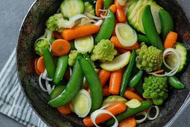 Vegetais veganos na frigideira, fritos ou prontos para cozinhar na mesa