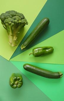 Vegetais verdes ajustados em um verde geométrico. dieta de baixa caloria