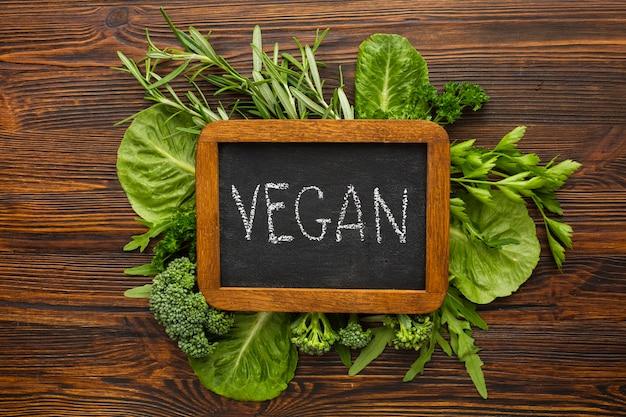 Vegetais verdes com letras vegan na lousa