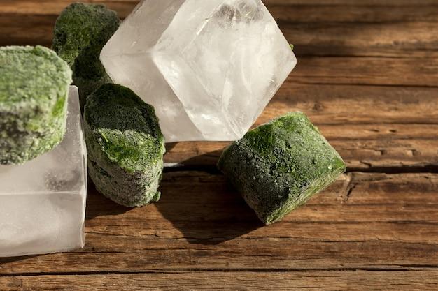 Vegetais verdes congelados, cubos de gelo e um copo transparente em uma velha mesa de madeira