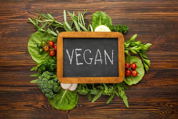 Vegetais verdes de vista superior com letras vegan na lousa