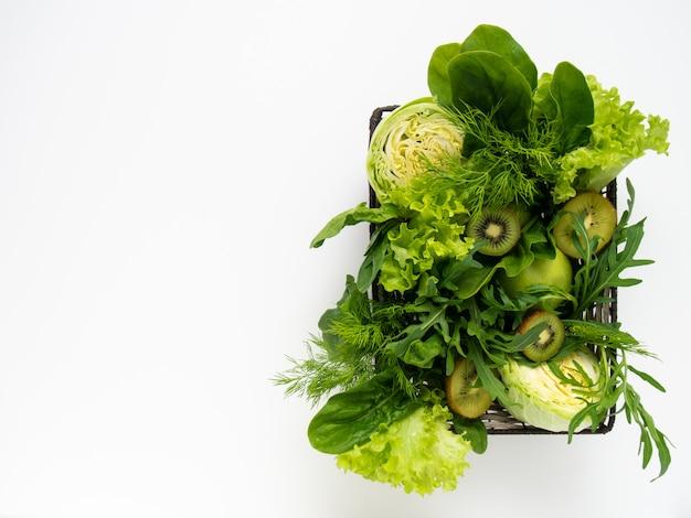 Vegetais verdes e frutas na cesta.