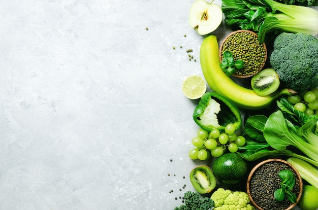 Vegetais verdes e frutas orgânicos no cinza. copie o espaço, leigo plano, vista superior. maçã verde, abobrinha, pepino, abacate, couve, limão, kiwi, uvas, banana, brócolis, lentilhas marmorizadas, feijão mungo
