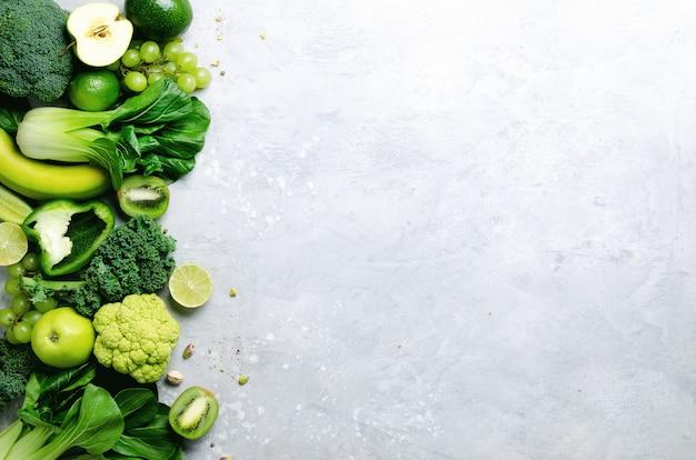 Vegetais verdes e frutas orgânicos no cinza. copie o espaço, leigo plano, vista superior. maçã verde, alface, abobrinha, pepino, abacate, couve, limão, kiwi, uvas, banana, brócolis