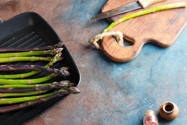 Vegetais verdes e roxos orgânicos naturais frescos do aspargo em uma bandeja pronta para cozinhar o alimento saudável em uma parede de pedra.