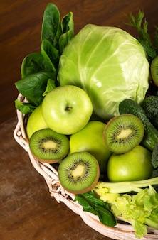 Vegetais verdes em uma cesta com fundo de madeira
