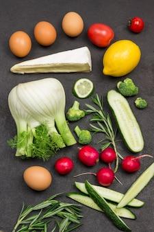 Vegetais verdes, erva-doce, brócolis, pepinos, raminhos de ovos de alecrim e hortelã, limão, queijo.