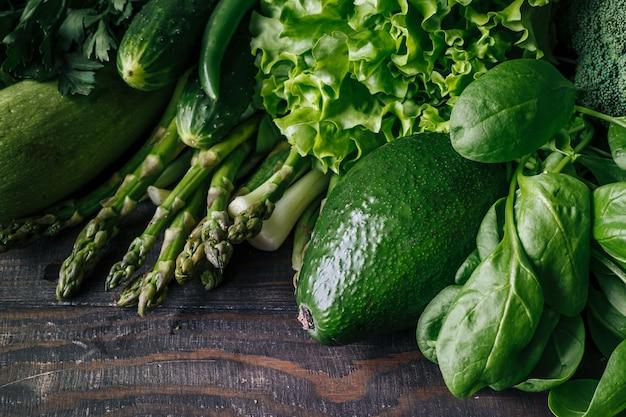 Vegetais verdes frescos, abacate, brócolis, espinafre, pepino, repolho, alface em uma mesa de madeira.