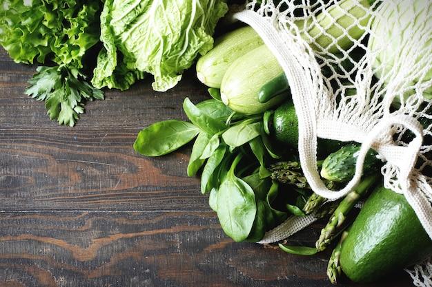 Vegetais verdes frescos, abacate, brócolis, espinafre, pepinos em uma vista superior do saco de malha.