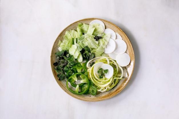 Vegetais verdes frescos e ervas com espaguete de abobrinha, vista de cima