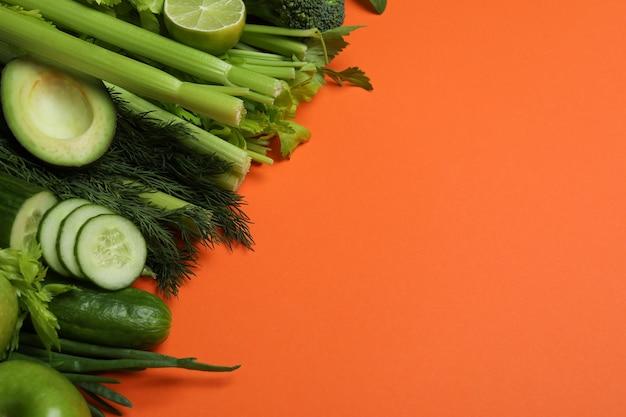 Vegetais verdes frescos em fundo laranja