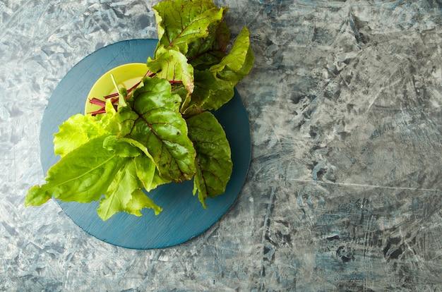 Vegetais verdes na bacia amarela em uma placa de madeira. salada com beterraba sorrel em um textured.